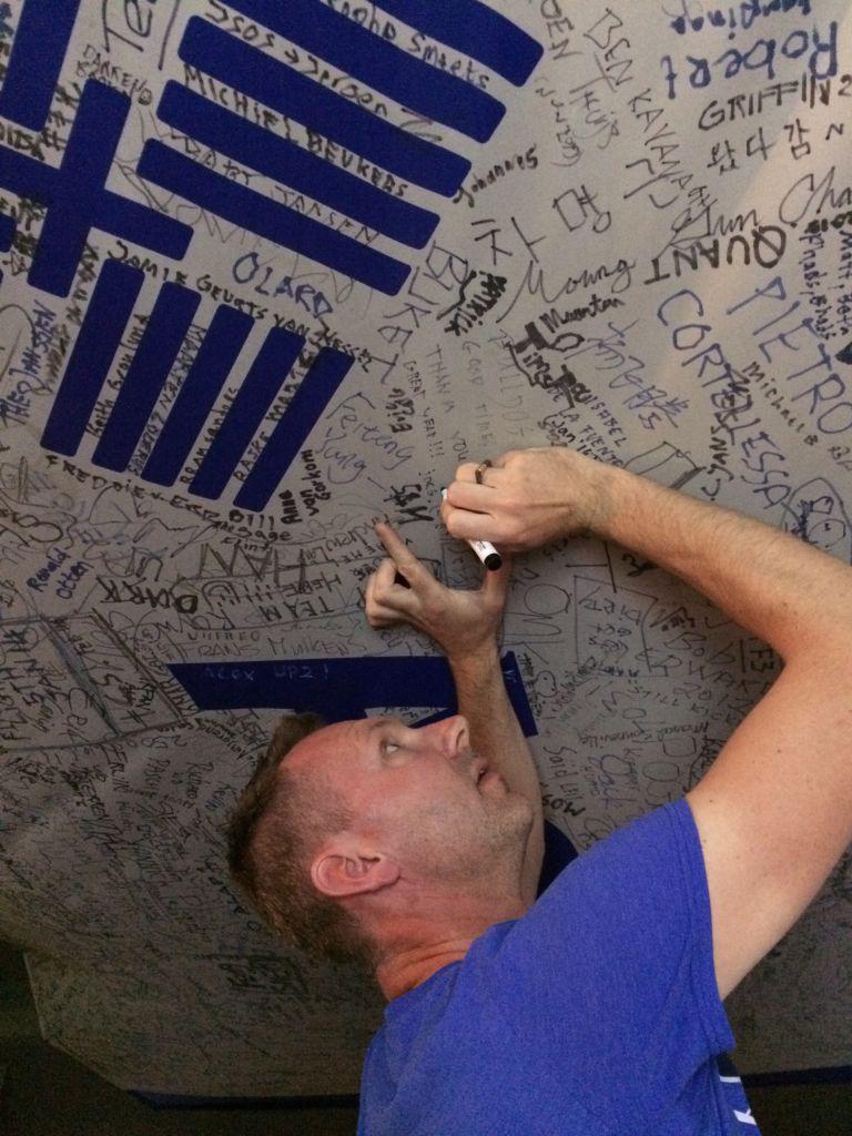 Majkel schrijft z'n naam op de al overvolle ASML vlag